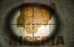 Sniper scope aimed at the vintage nigerian flag and map Stock Illustration