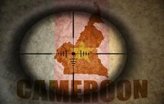 sniper scope aimed at the vintage cameroon flag and map - stock illustration