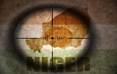 Stock Illustration of sniper scope aimed at the vintage niger flag and map