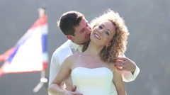 Groom speaks in  bride's ear and tickles against flag Stock Footage