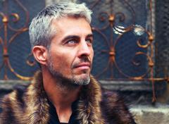 Portrait of a sexy man in wolf  fur and ornamental medieval window on background Stock Photos