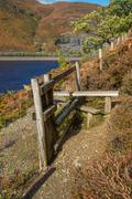 Wooden  Stile Style, over fence, with bracken. Lake and mountain - stock photo