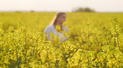 Girl running happy in Brassica rapa canola field at sunset - stock footage