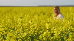 Girl running happy in Brassica rapa canola field at sunset Stock Footage