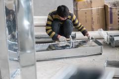 Asian Construction Worker Hammering Air Duct Stock Photos