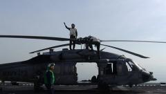 Squadron Plane Inspectors inspect Helicopter on Carrier Deck Stock Footage