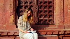 Young female tourist reads guide book at Indian architecture 4k Stock Footage