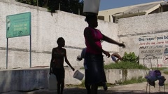 Woman Carrying Water in Bucket on Head Stock Footage