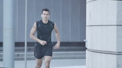 Man running in urban environment marble wall in the background 2 Stock Footage