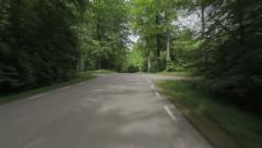 Car driving on a paved road through a beech forest Stock Footage