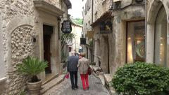 Tourists walk along the narrow street of St Paul de Vence, France Stock Footage