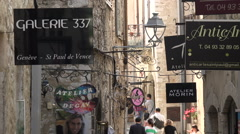 Zoom out from boutique shop signs in street of St Paul de Vence, France Stock Footage