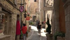 Tourists visit shops in narrow street of Saint Paul de Vence, France Stock Footage