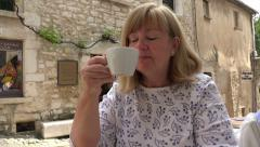 Senior woman tourist drink coffee in cafe in Saint Paul de Vence, France Stock Footage