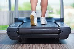 Fitness girl running on treadmill. Woman with muscular legs in gym Stock Photos
