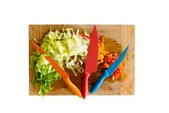 Knives on Cutting Board with Chopped Veggies - stock photo