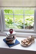 Coffee on Piled Books and Pastries at the Window - stock photo
