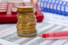 Stack of coins and pen on financial report, close up Stock Photos