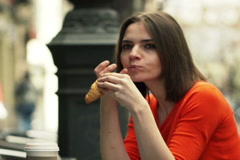 Beautiful woman eating croissant sitting in cafe in city NTSC Stock Footage