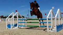 Rider on horse jumps over barrier Stock Footage