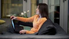 Woman finishing working on laptop, stretching and yawning on sofa at home HD Stock Footage