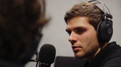 Radio interview, a young man with mic in studio, radio interview Stock Footage