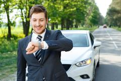 Young businessman checking time near car Stock Photos