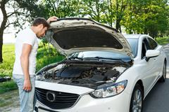 Man standing in front of opened bonnet - stock photo