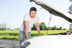 Man leaning on car with opened bonnet - stock photo