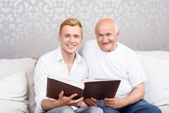 Grandfather and grandson sitting with album - stock photo