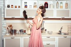 The girl looks into the pan. - stock photo