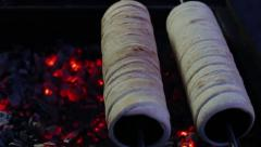 Chimney cake baking over charcoal fire outdoors Stock Footage