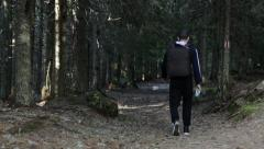 Man walking in the woods through a touristic path Stock Footage
