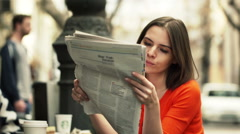 Young woman reading newspaper while sitting in cafe in city  HD Stock Footage