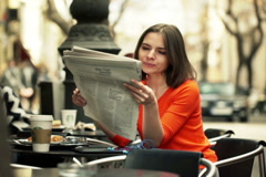 Young woman reading newspaper while sitting in cafe in city NTSC Arkistovideo