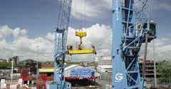 Industrial crane loading and unloading cargo containers at a busy port. - stock footage