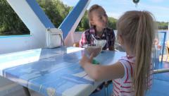 Girl treats mom ice cream on  floating pleasure river boat - stock footage