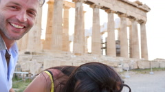 Beautiful Greek couple takes a selfie with Greek architecture in the background. Stock Footage