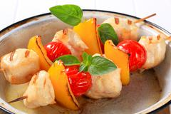 Grilled chicken chunks with cherry tomatoes and yellow pepper on skewers Stock Photos