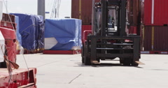 Stock Video Footage of Forklift handling shipment at a busy industrial port.