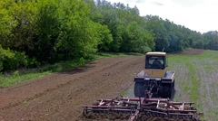 Stock Video Footage of Farm equipment cultivating a field in preparation for spring planting