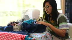 Asian women use machine sewing clothes - stock footage