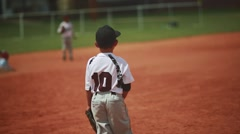 Kid standing in uniform during a baseball game Stock Footage