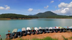 Da Lat - May 2015: Turquoise lake with boats leaving dock. 4K speed up. Stock Footage