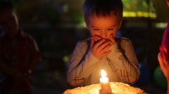 Close-up portrait of a little boy blows out the candles on the cake Stock Footage