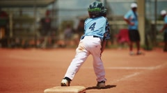 Kid standing on base during a baseball game Stock Footage