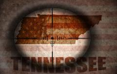 sniper scope aimed at the vintage american flag and tennessee state map - stock illustration