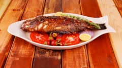 Main course: whole fried seabass served on wood Stock Footage