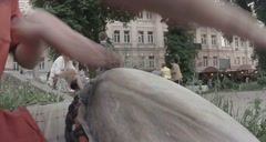 Street musician playing on a makeshift drum among people passing by Stock Footage