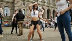 Girls dancing waving rainbow flag at gay parade Stock Footage